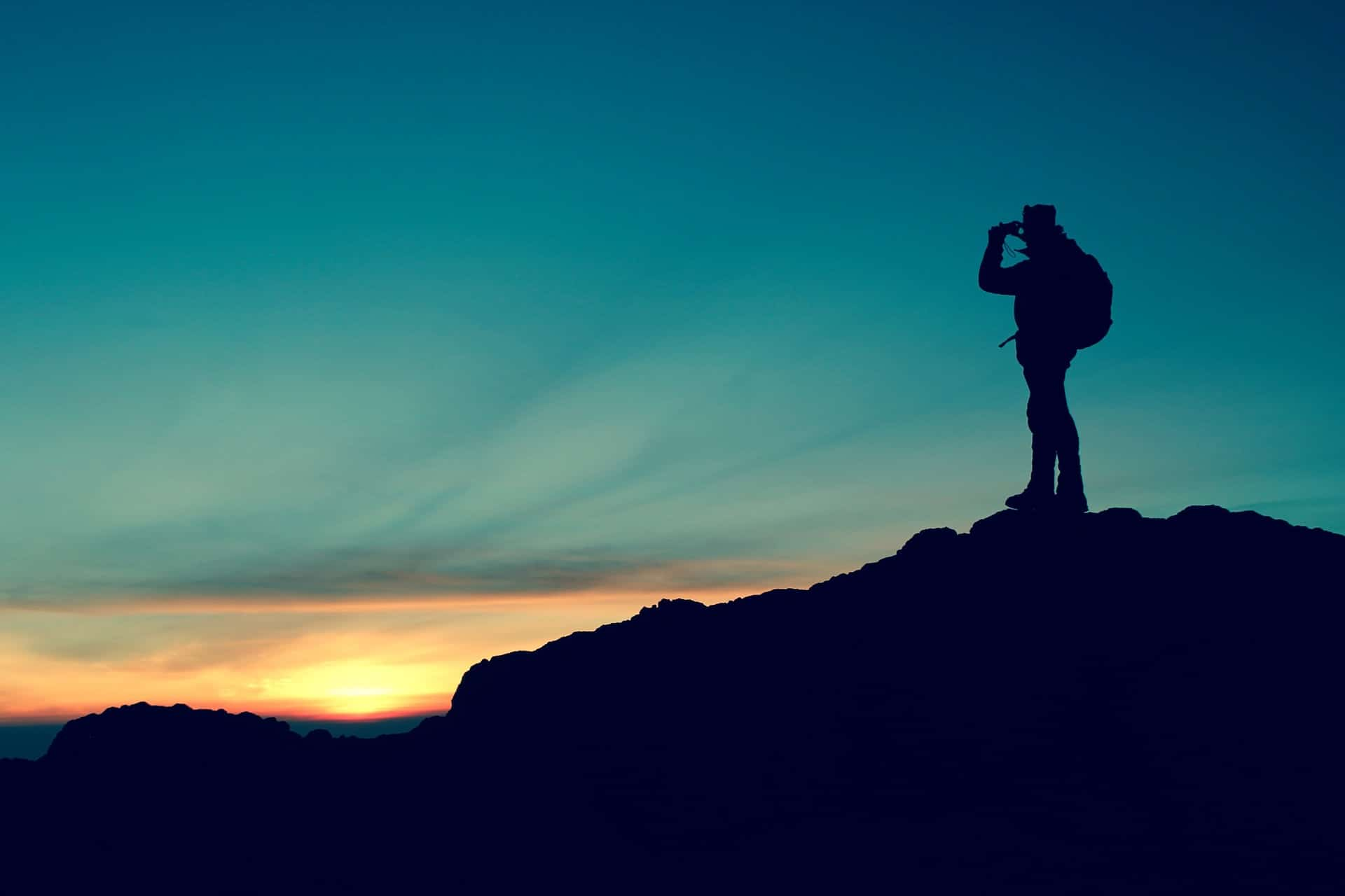 A man on top of mountain with binoculars on