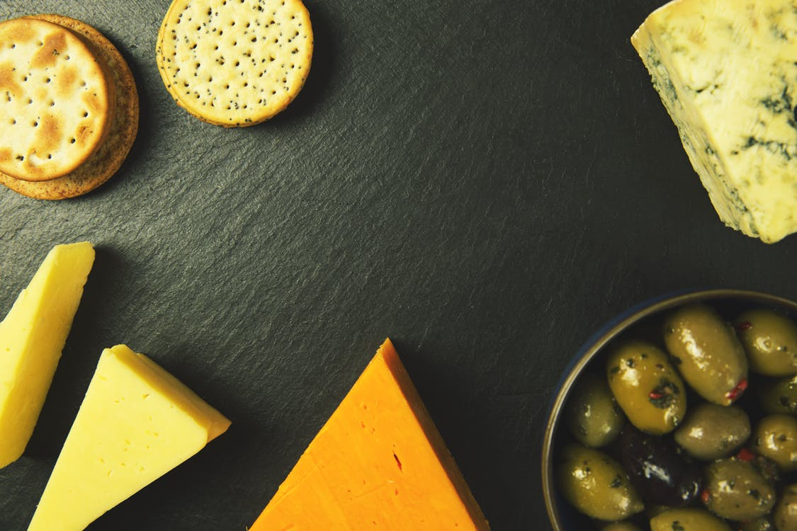 top view of cheese and crackers on a black surface