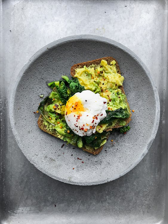top view of poached egg on top of toast with avocado