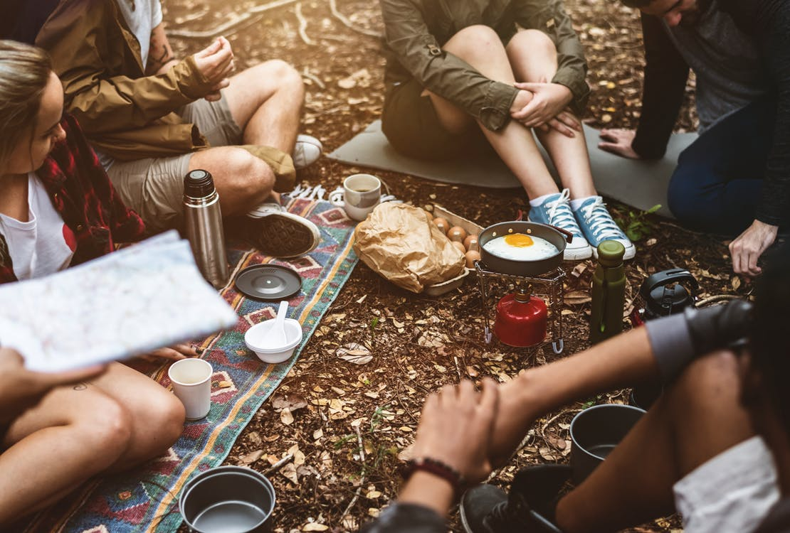 campers sharing a meal while seated on the ground