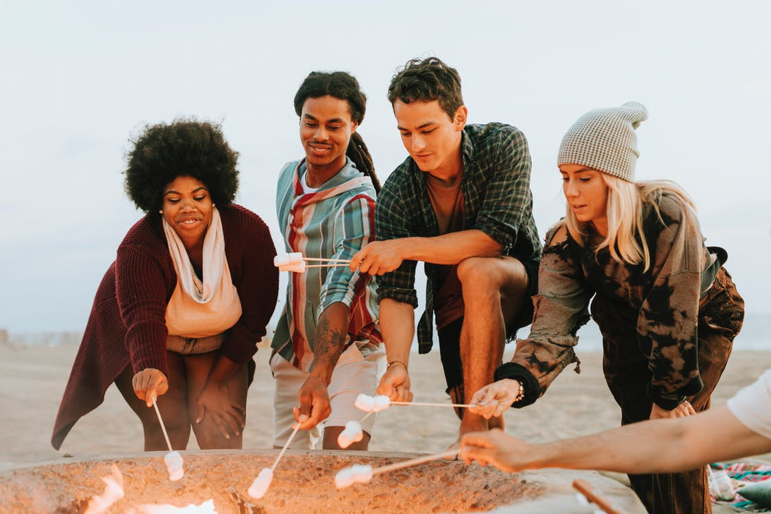 four people toasting marshmallows on the bonfire