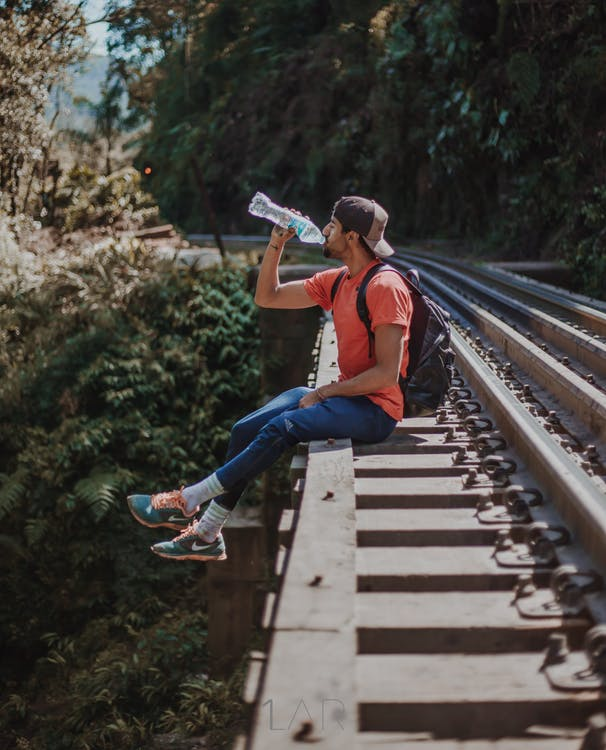 man sitting on the rails drinking water