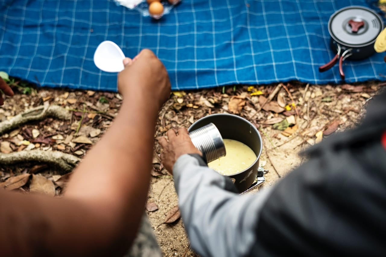 camper pouring soup from a can
