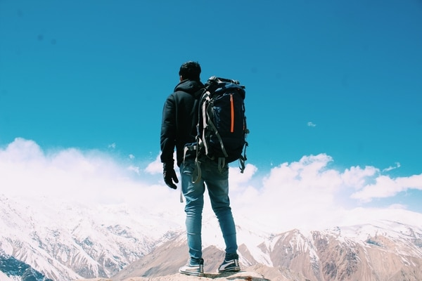 guy standing on top of the mountain with hiking backpack