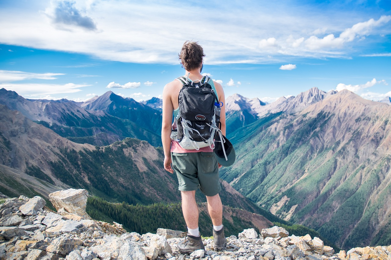 A guy looking on a scenic view of mountains